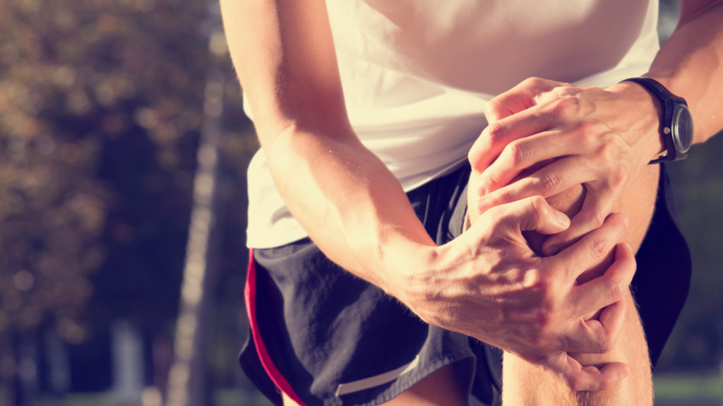 Man exercising with severe joint pain