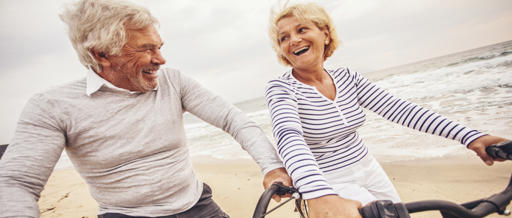 elderly couple riding bikes on the beach