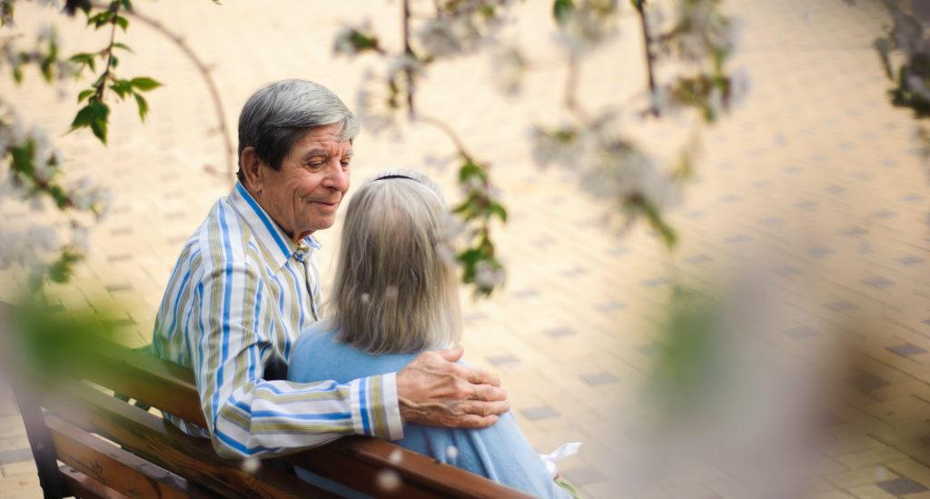 elderly couple talking on a park bench