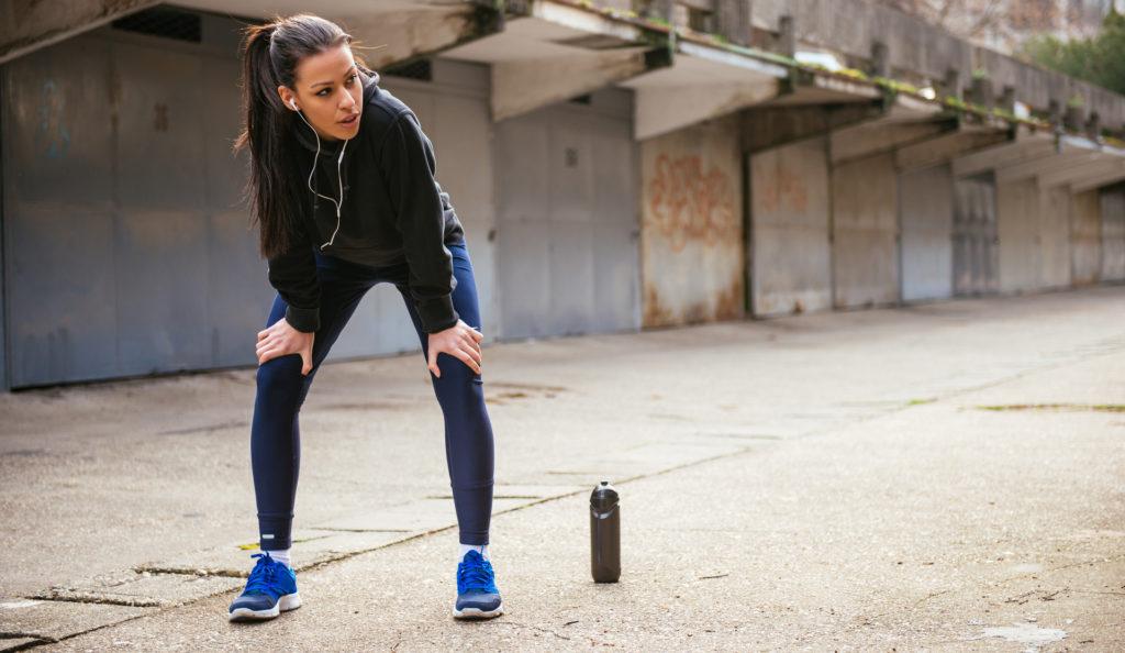 Women exercising outside listening to music