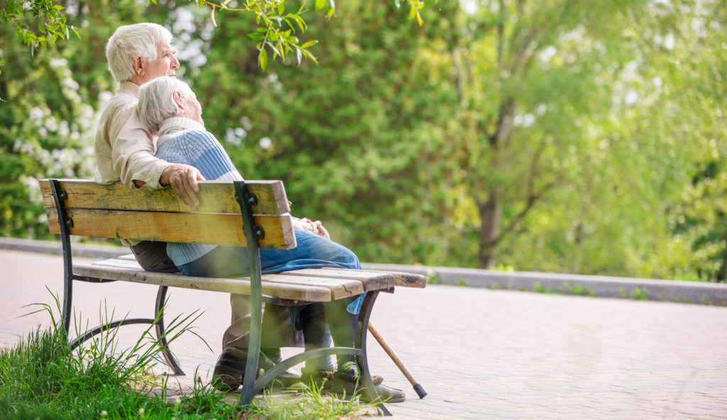 elderly couple with a cain sitting on a park bench