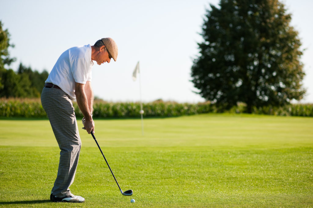 active middle aged man playing golf