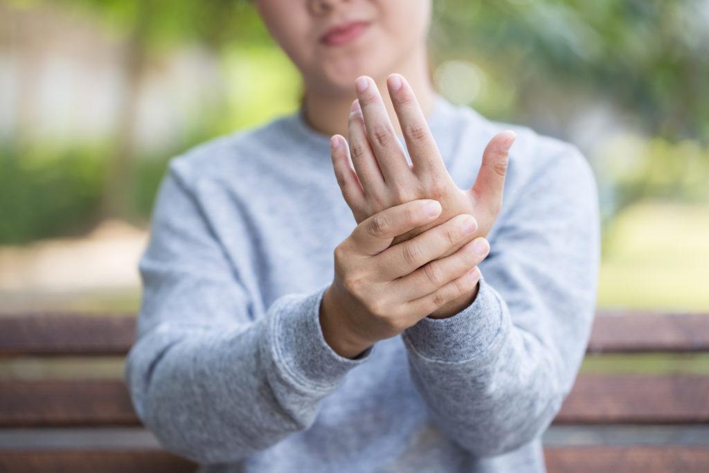 Women massaging her hand to relieve arthritis pain