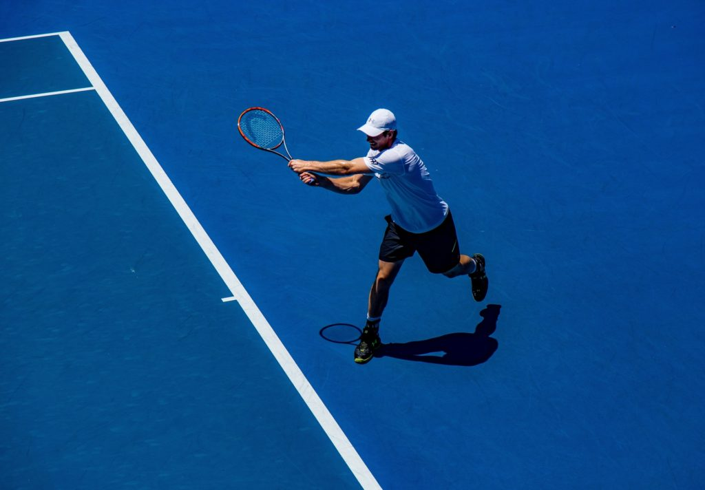 Tennis player on blue court leaning heavily on his ACL
