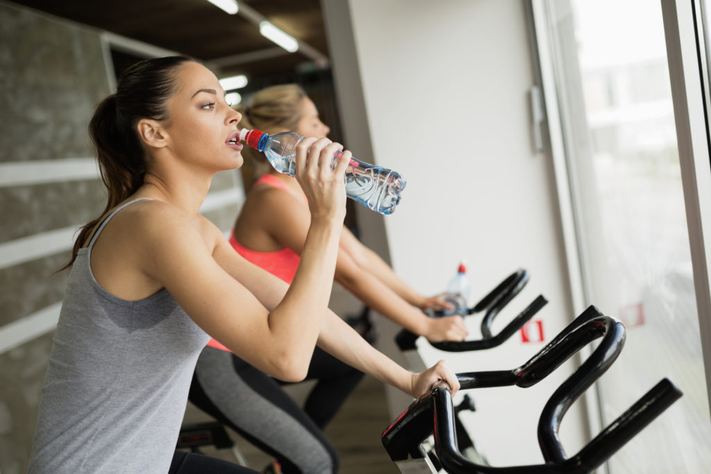 two women on exercise bikes hydrating with water