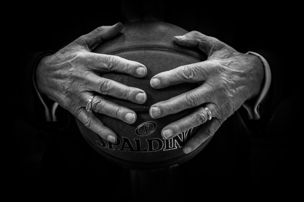older hands holding a basketball black and white